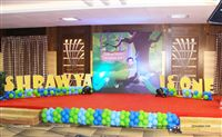 Backdrop on the stage with a caricature of the birthday girl and peacocks in a jungle scene. Alphabet blocks with the babys name on either side of the backdrop and a string of balloons at the base