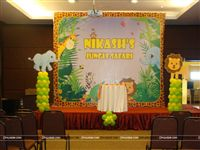 Stage setup for a Jungle Birthday party with a 8 feet backdrop and two balloon pillars on either side along with an Elephant and Lion cutout.